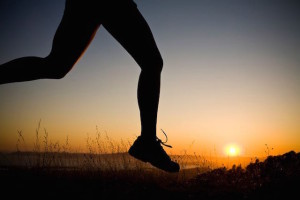 A silhouetted woman runs at sunset.